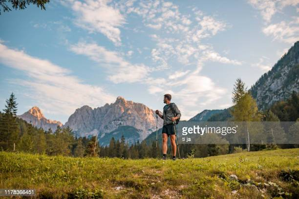 adult man hiking with hiking poles in mountains stock photo - slovenia stock pictures, royalty-free photos & images