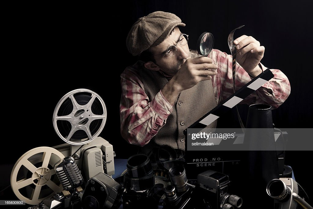 Adult Man Holding Cinema Film And Checking With Magnifying Glass : Stock Photo