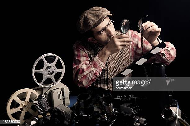 Adult Man Holding Cinema Film And Checking With Magnifying Glass