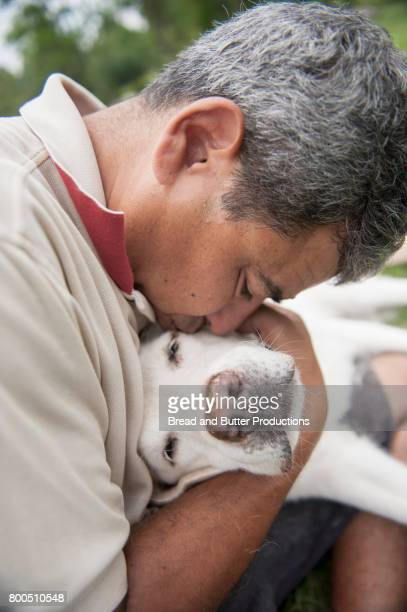 Adult Man hugging his Yellow Labrador Retriever