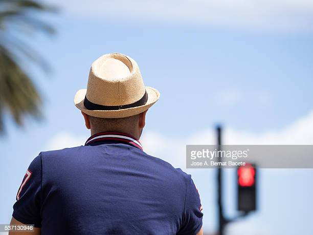 Adult man in bicycle and with hat of straw, stopped opposite to a red semaphore