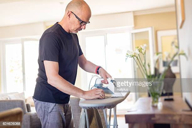 Adult man ironing his shirt at home