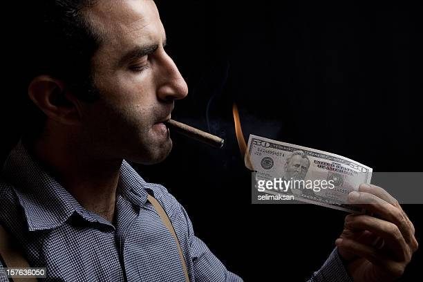 Adult man lighting up a cigar with burnt dollar bill