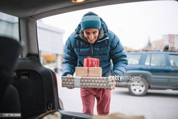 adult man loading christmas presents in car trunk. - boxing day stock pictures, royalty-free photos & images