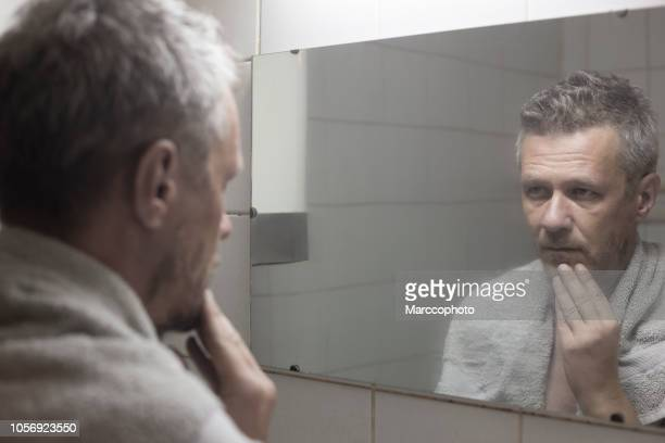 adult man looking at his face in bathroom mirror - vanity mirror stock photos and pictures