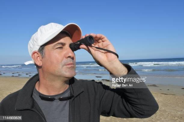 adult man looking through monocular - rafael ben ari stockfoto's en -beelden
