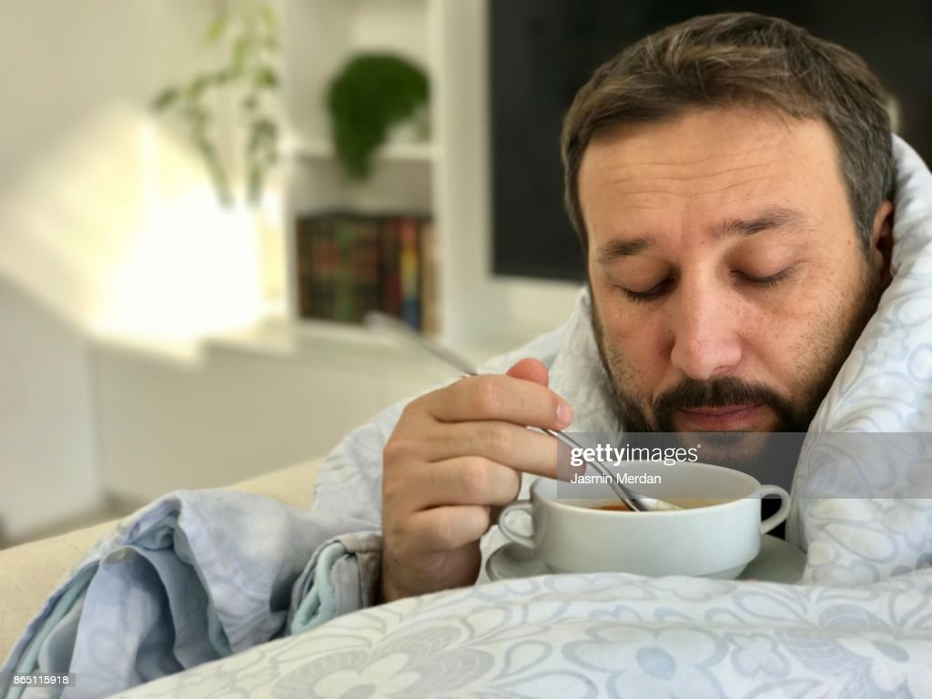 Adult man lying sick on sofa in living room eating soup with no taste : Stock Photo