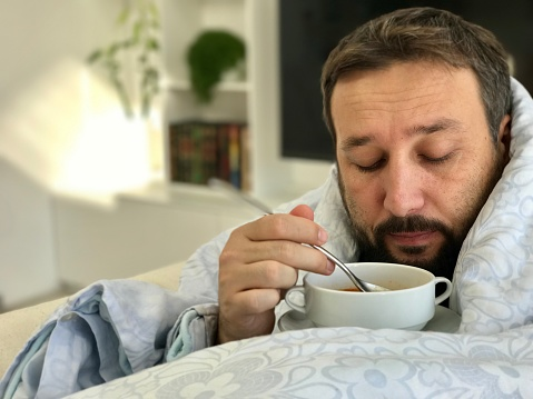Adult man lying sick on sofa in living room eating soup with no taste - gettyimageskorea