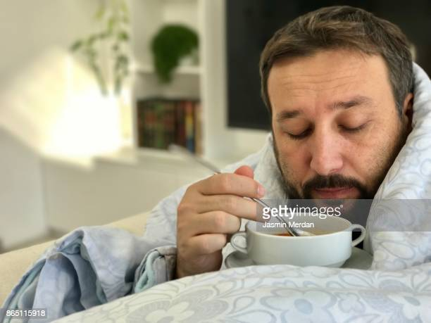 adult man lying sick on sofa in living room eating soup with no taste - cold and flu stock photos and pictures