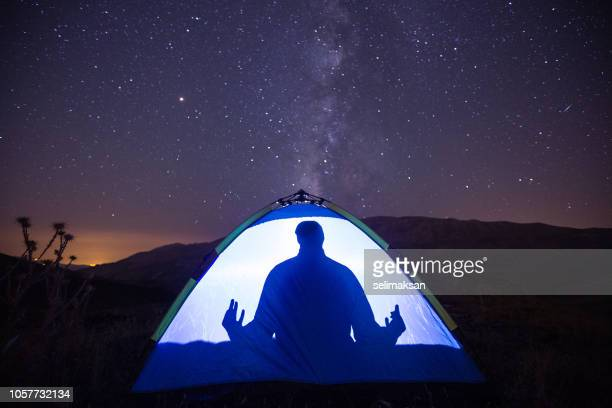 Adult Man Meditating In Camping Tent Under Milky Way