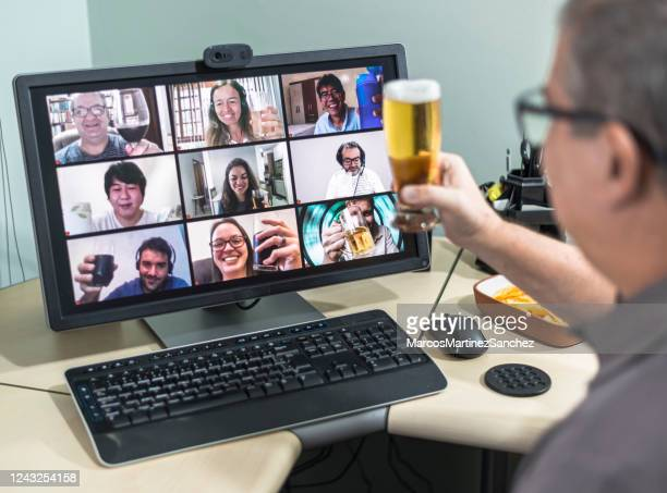 adult man on conference call drinking beer with friends doing happy hour - happy hour stock pictures, royalty-free photos & images