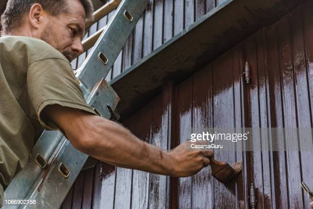 adult man painting an old house with protective paint - painting stock pictures, royalty-free photos & images