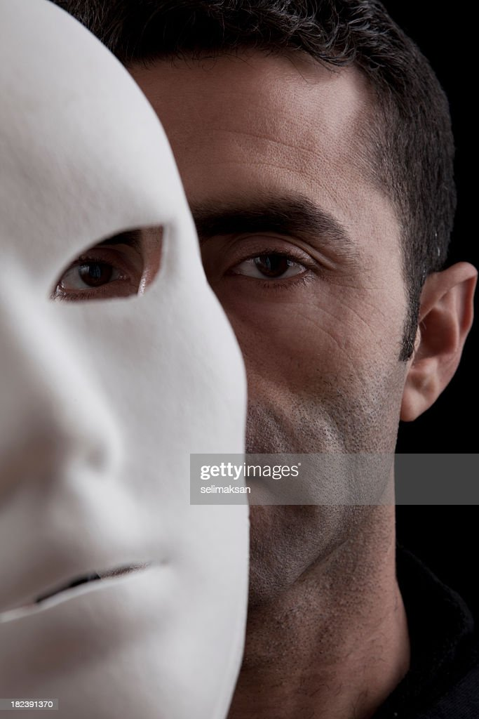 Adult Man Peeking Behind Mask In Vertical Composition : Stock Photo