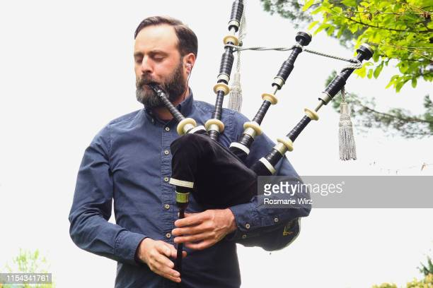 adult man playing scottish bagpipe - bagpipes stock pictures, royalty-free photos & images