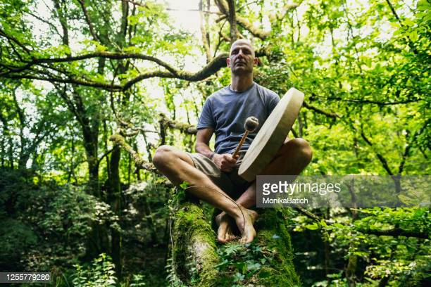 adult man playing shamanic drum - chanting stock pictures, royalty-free photos & images