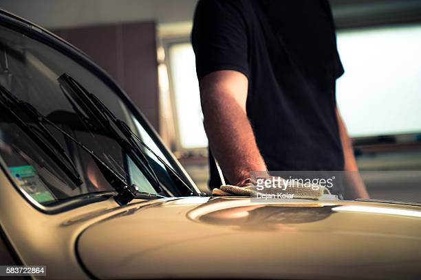 Adult man polishing oldtimer car in workshop with cleaning cloth