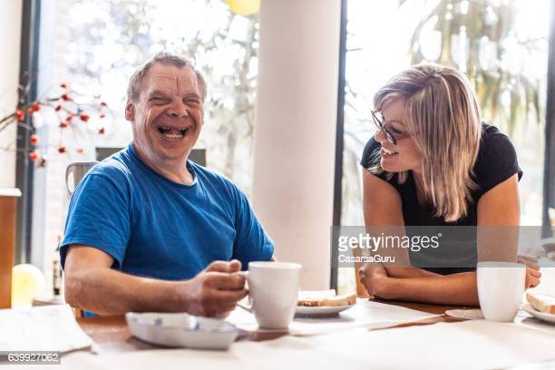adult man portrait with a down syndrome and a caregiver - gezondheidszorg beroep stockfoto's en -beelden