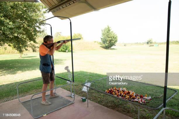 adult man practicing skeet shooting at shooting range - trap shooting stock pictures, royalty-free photos & images