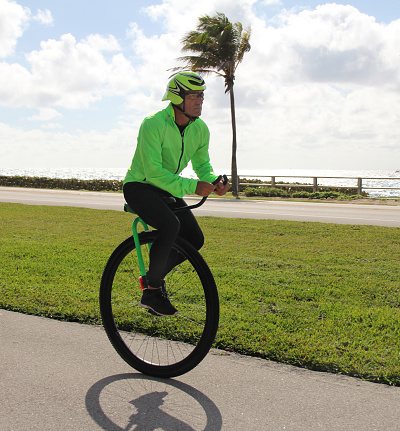 Adult man riding a unicycle near the beach - gettyimageskorea