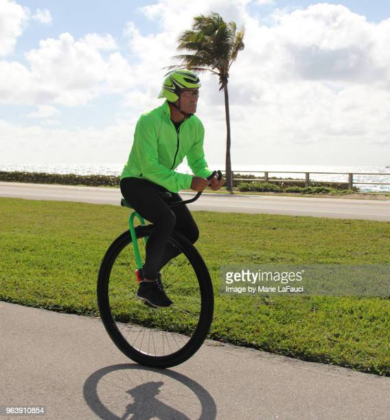 Adult man riding a unicycle near the beach