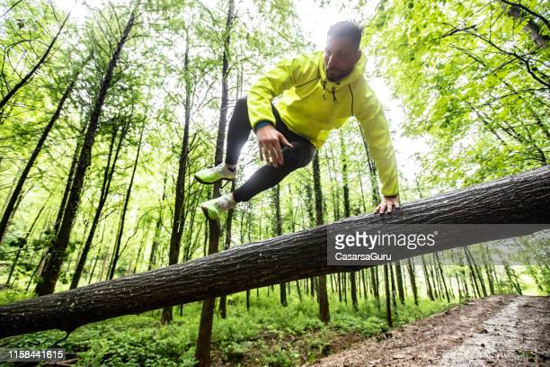 adult man running in forest in bad weather - active lifestyle stock pictures, royalty-free photos & images