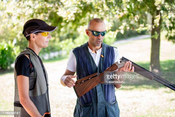 adult man showing adult woman how to handle a shotgun - stock photo - clay pigeon shooting stock pictures, royalty-free photos & images