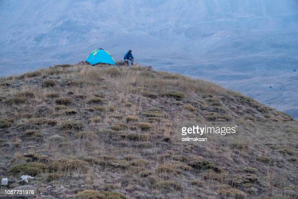 Adult Man Standing By Camping Tent On Top Of Hill