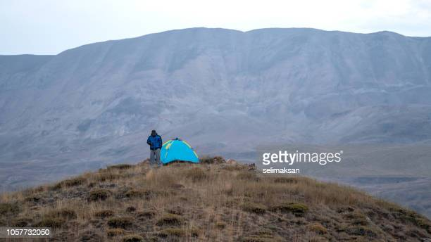 adult man standing by camping tent on top of hill - wilderness area stock pictures, royalty-free photos & images