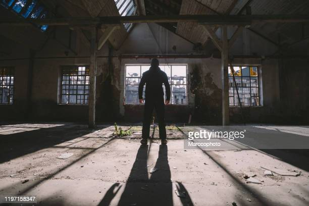 adult man standing inside some large, dark, spooky,abandoned building illuminated with sunlight through window - serial killings stock pictures, royalty-free photos & images