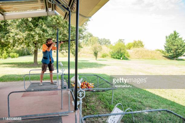 adult man standing on firing lane and practicing skeet shooting - trap shooting stock pictures, royalty-free photos & images