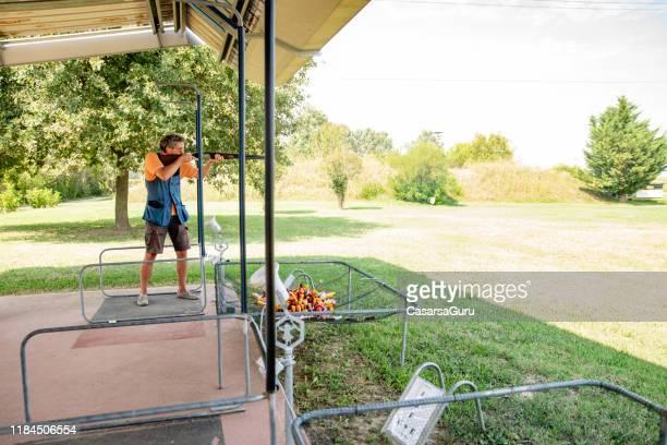 adult man standing on firing lane and practicing skeet shooting - shotgun stock pictures, royalty-free photos & images
