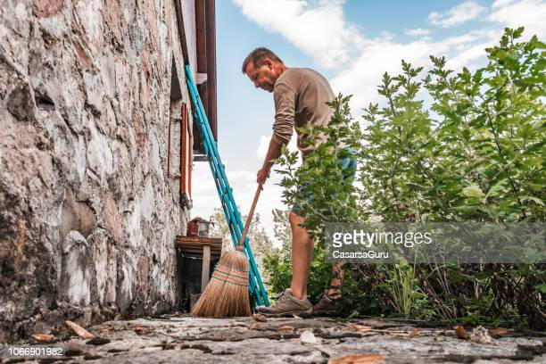 adult man sweeping front yard in rural scene - sweeping stock pictures, royalty-free photos & images