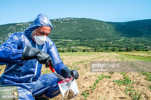adult man taking a soil sample on agriculture field - heavy metal stock photos and pictures