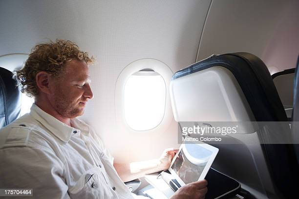 Adult man using a digital tablet on the plane