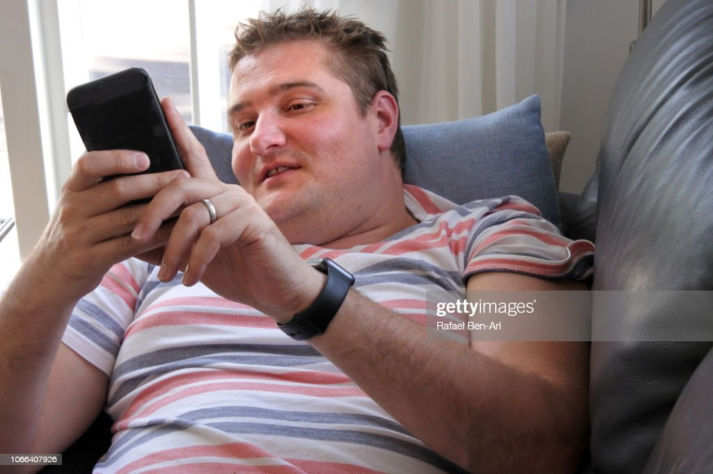 Adult Man Using his Mobile Phone at Home : Stock Photo