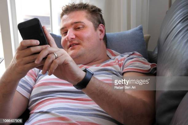 Adult Man Using his Mobile Phone at Home