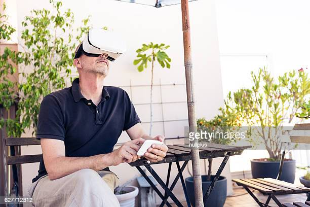 Adult man using VR goggles on his balcony