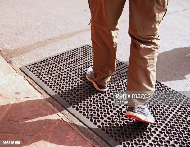 Adult man wearing convertible travel pants walking on metal grid drain cover