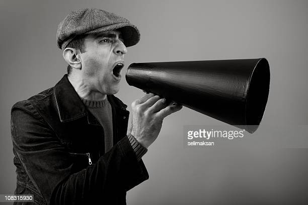 Adult Man Wearing Flat Cap Shouting On Old Fashioned Megaphone