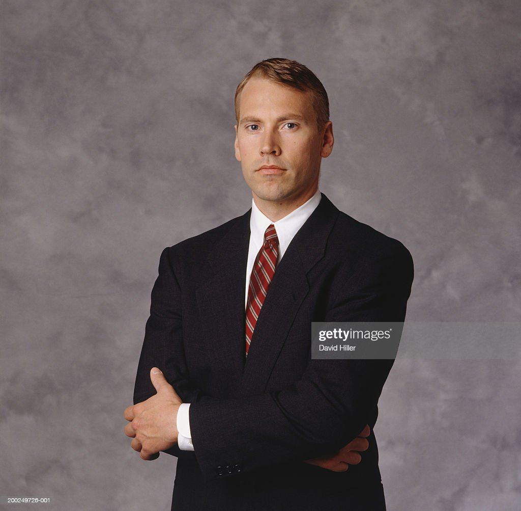 Adult man wearing suit, arms crossed : Stock Photo