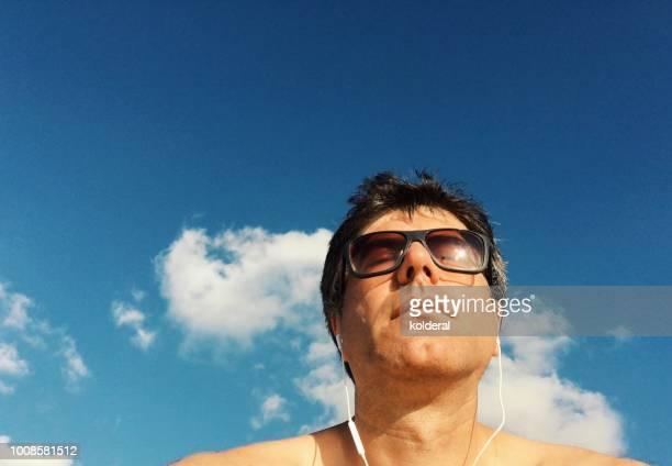 Adult man wearing sunglasses and white earphones sunbathing against blue sky .