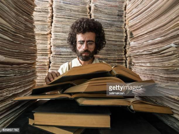 erwachsener mann mit dunklen haaren lesebuch in gedruckten medien-archiv - bibliothekar stock-fotos und bilder