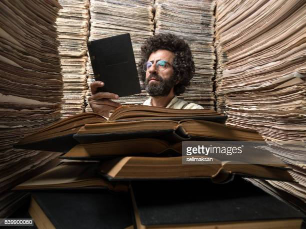 adult man with dark hair reading book in printed media archive - publication stock pictures, royalty-free photos & images