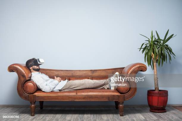 adult man with vr headset lying down on psychiatrist couch - cyberspace stock pictures, royalty-free photos & images