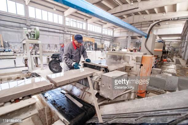 homem adulto que trabalha na linha de produção de uma fábrica de processamento de pedra - foto conservada em estoque - mármore rocha - fotografias e filmes do acervo