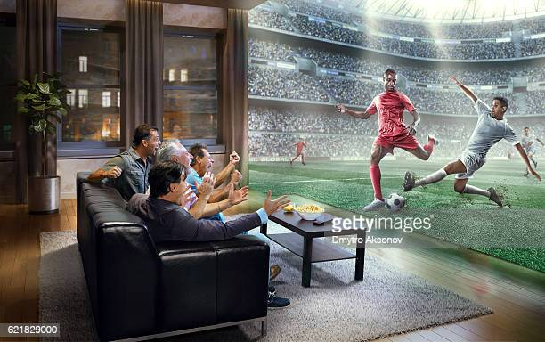Adult men are watching very realistic Soccer game on TV