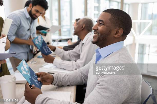 adult men hand out information at a conference - pamphlet stock pictures, royalty-free photos & images