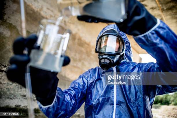 adult men taking a scientific sample of waste water - gas mask stock pictures, royalty-free photos & images