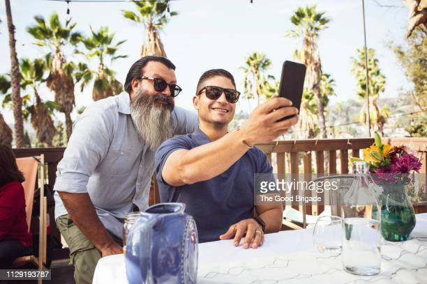 Adult men taking selfie in backyard