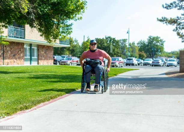 adult millennial male college student in wheelchair on sidewalk near dormatory - college admission stock pictures, royalty-free photos & images